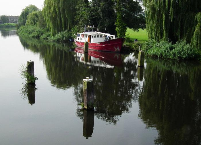 Foto van bootje en spiegeling van bomen