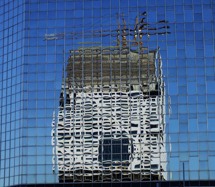 Foto van reflectie van gebouw in ander, glazen gebouw